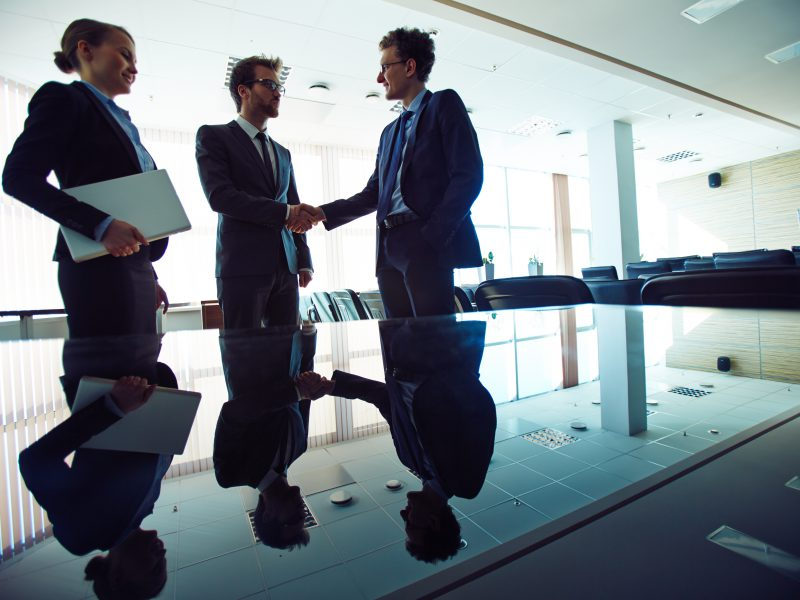 Successful professionals handshaking in office with young businesswoman near by